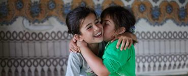 Two young children hugging in front of colourful screen
