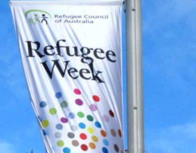 Flag of Refugee Week against blue sky